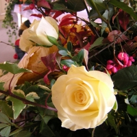 Edle Rosen und Pfaffenhütchen in einem herbstlichen Gesteck